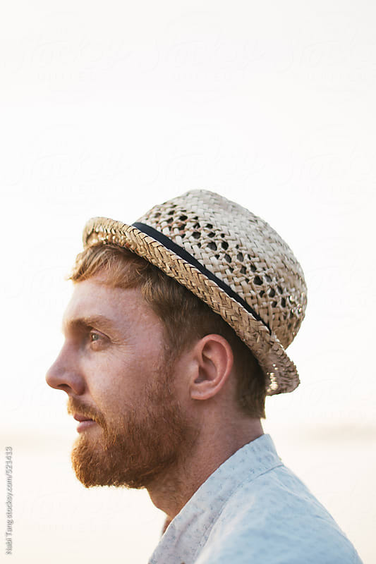 Handsome hipster with the straw hat by the sea by Nabi Tang for Stocksy United