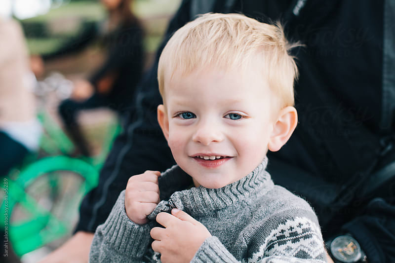 A little blonde boy unzipping a grey knit sweater and smiling. by Sarah Lalone for Stocksy United