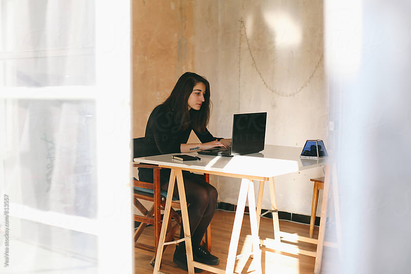 Brunette woman working on a laptop in her home office  by Marija Mandic for Stocksy United