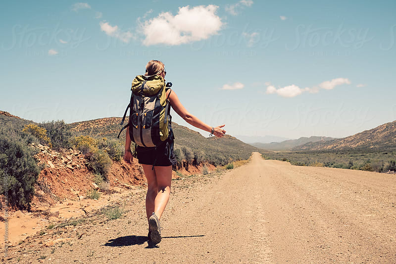 Woman hitchhiking on an empty dirt track through the Karoo by Micky Wiswedel for Stocksy United