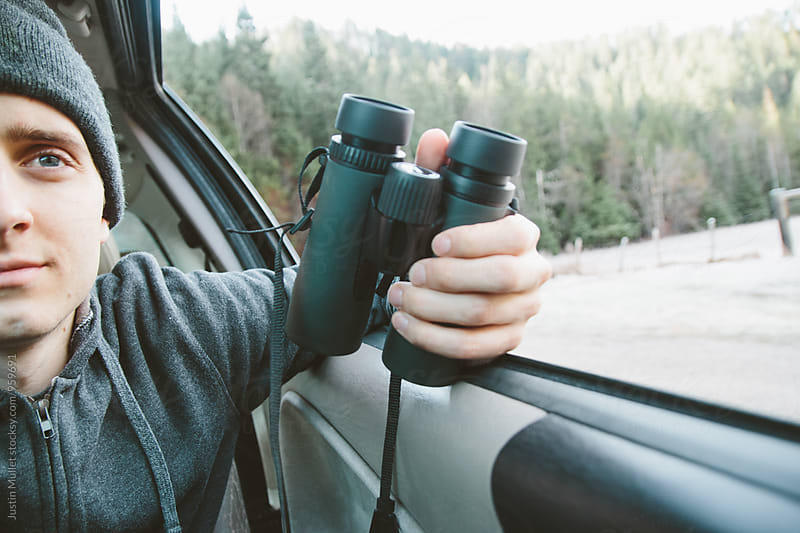 Close up of young man holding binoculars in a vehicle by Justin Mullet for Stocksy United