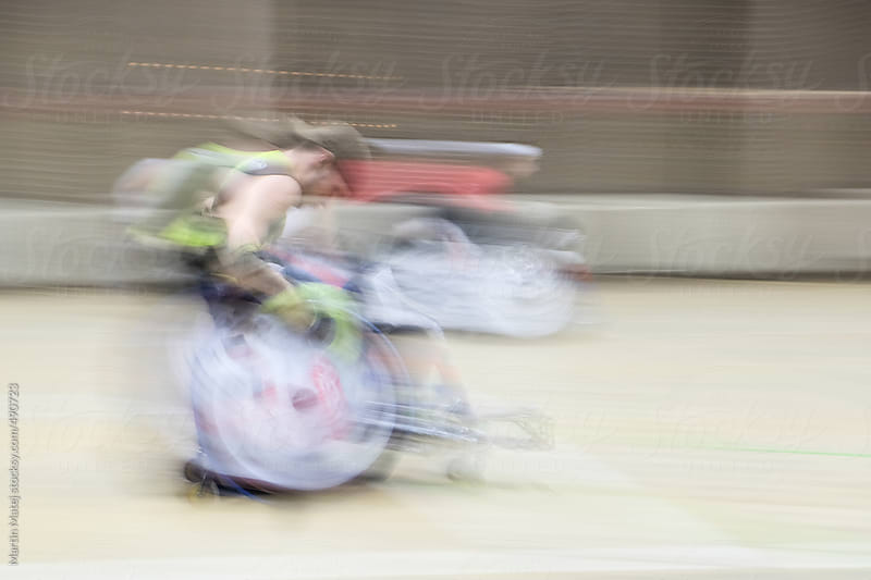 Athlete in wheelchair riding fast in gym by Martin Matej for Stocksy United