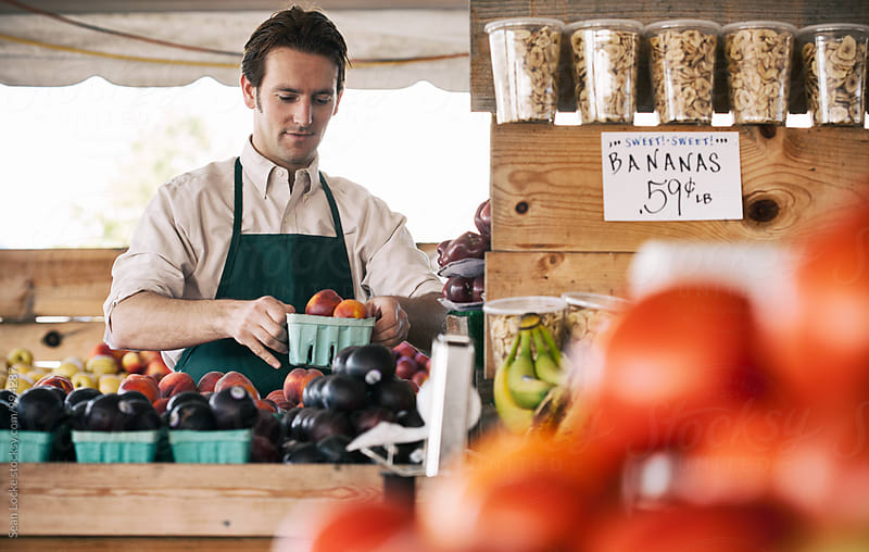 Market: Employee Arranging Produce On Table by Sean Locke for Stocksy United