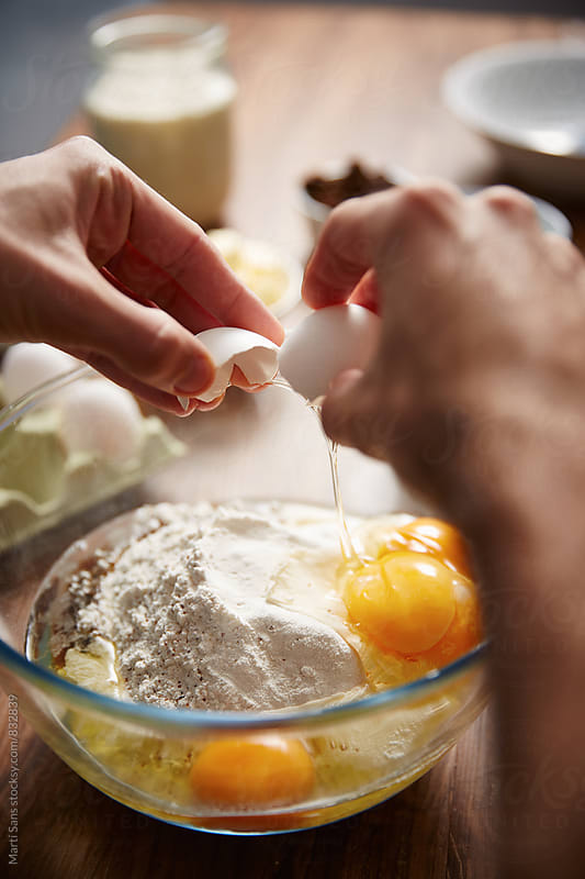 Close-up of man's hands adding eggs in flour, preparing panettone by Martí Sans for Stocksy United