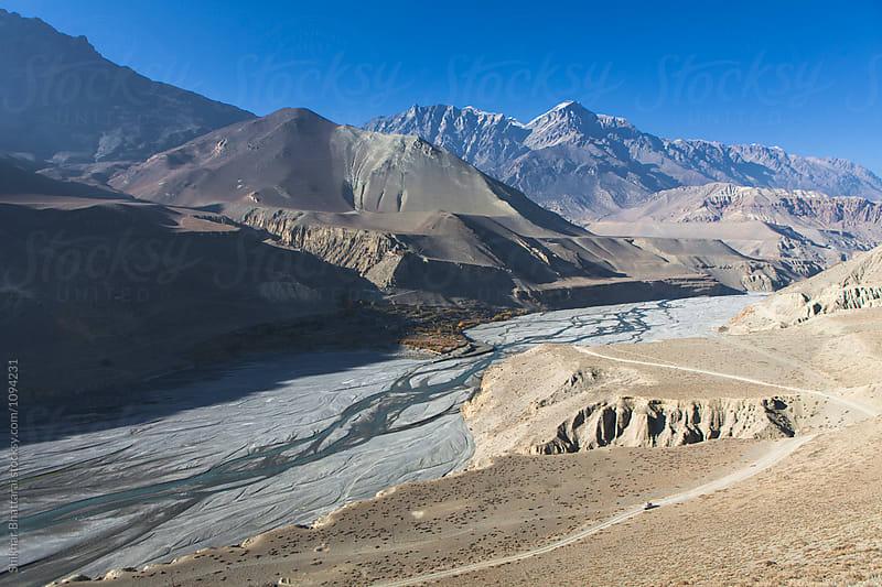 Kali Gandaki river bed with a jeep crossing the landscape. by Shikhar Bhattarai for Stocksy United