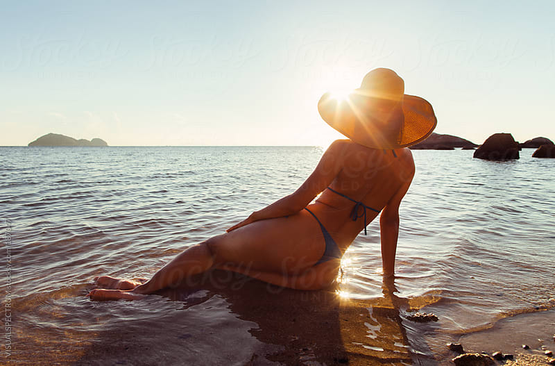 Sexy Woman Watching Sunset on Beach by VISUALSPECTRUM for Stocksy United