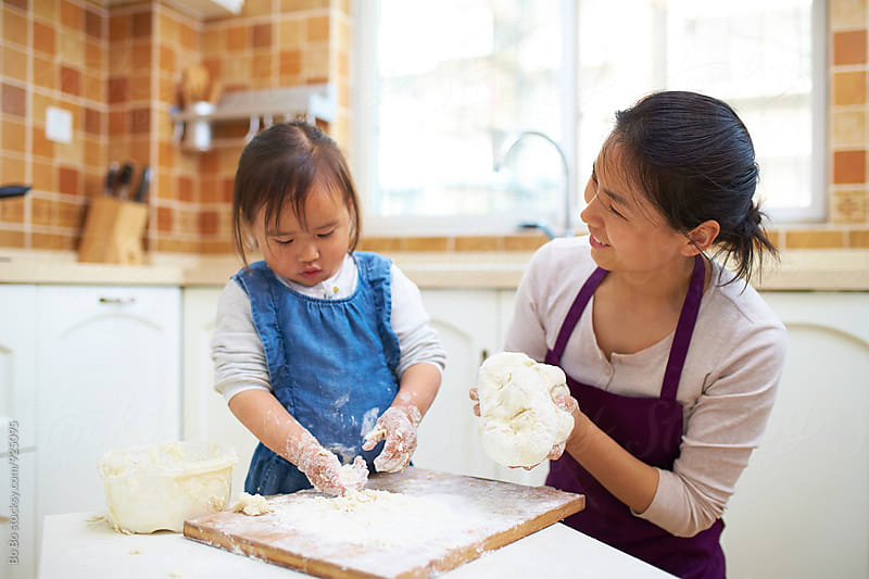 little asian girl making paste in kitchen with her mother by Bo Bo for Stocksy United