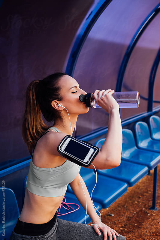 Attractive Fit Woman Drinking Water While Taking A Break by Katarina Radovic for Stocksy United