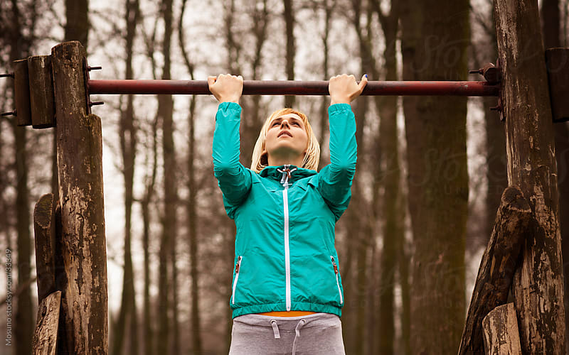 Young woman doing pull ups in the park on a rainy spring day.  by Mosuno for Stocksy United