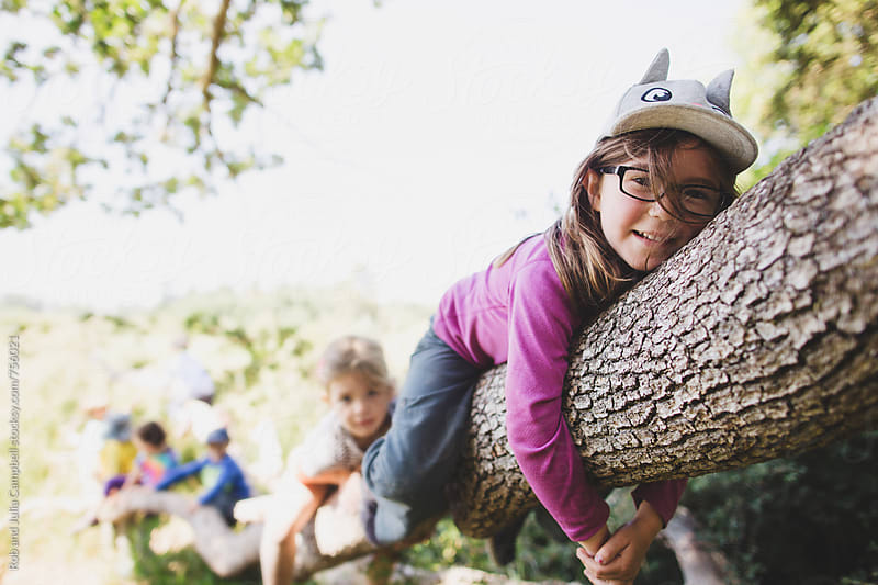 Cute girl having fun climbing tree in nature by Rob and Julia Campbell for Stocksy United