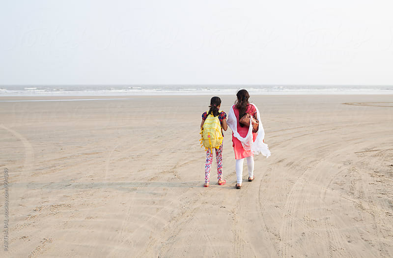 Mother and daughter waling in a remote beach by PARTHA PAL for Stocksy United