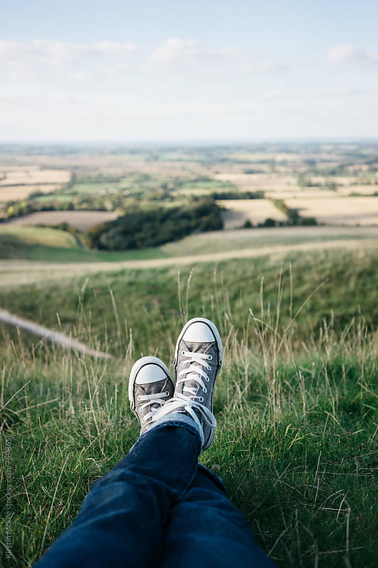 Shoes in the foreground of a view over Oxfordshire by Kirstin Mckee for Stocksy United