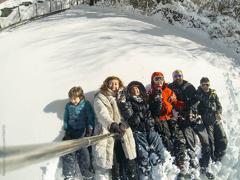 Parents with 4 kids taking a selfie in the snow by Beatrix Boros for Stocksy United