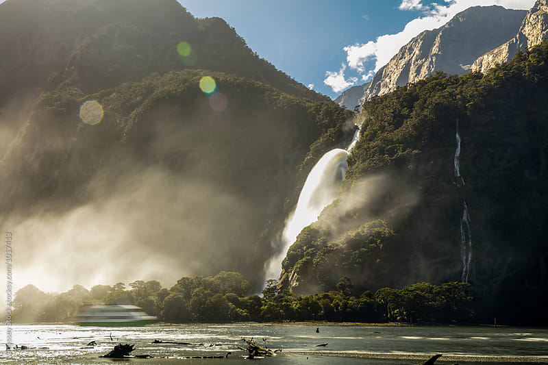 Ferry Boat Passing New Zealand Waterfall by Odyssey Stock for Stocksy United