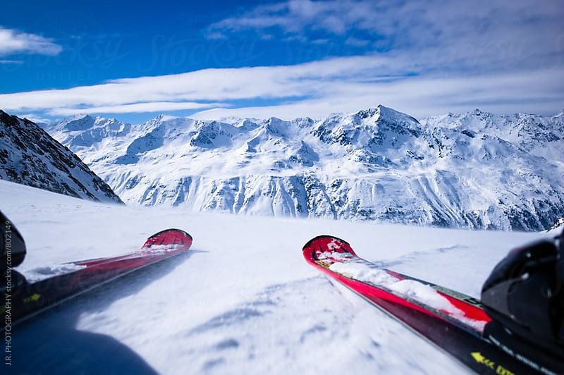 Skiing downhill at high speed against the mountains by J.R. PHOTOGRAPHY for Stocksy United