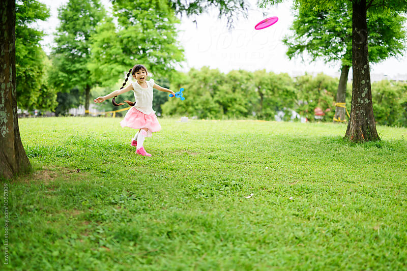 Happy girl playing frisbee in park by Lawren Lu for Stocksy United