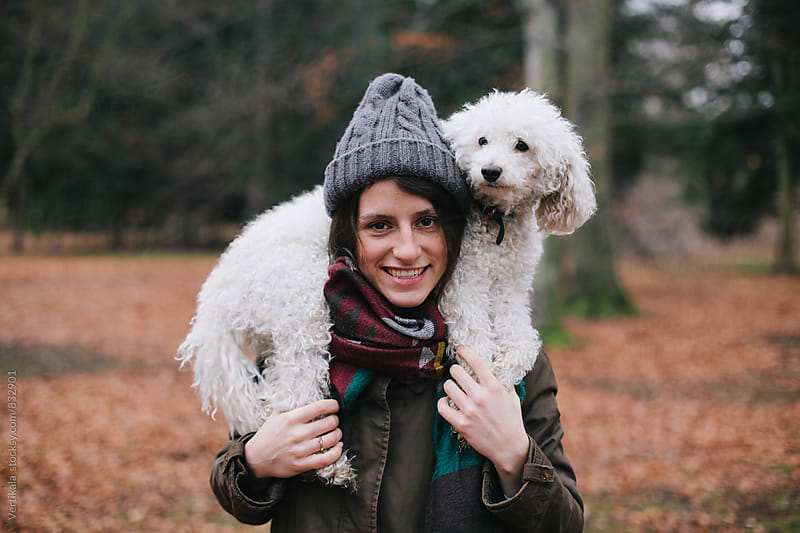 Portrait of a beautiful happy woman with her white dog in nature by Marija Mandic for Stocksy United