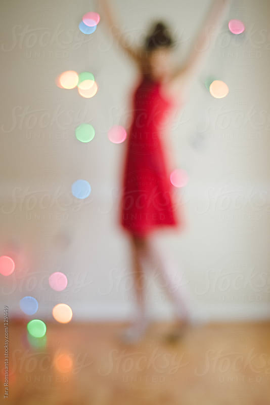 bokeh red dress woman and holiday lights by Tara Romasanta for Stocksy United