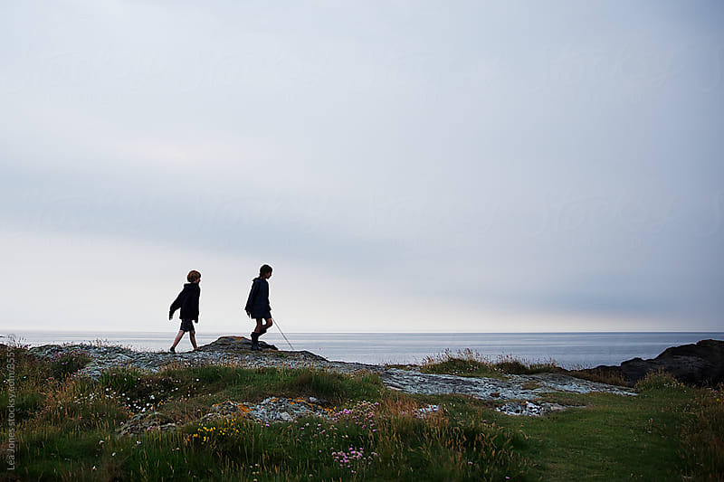 Two kids walking by the sea by Léa Jones for Stocksy United