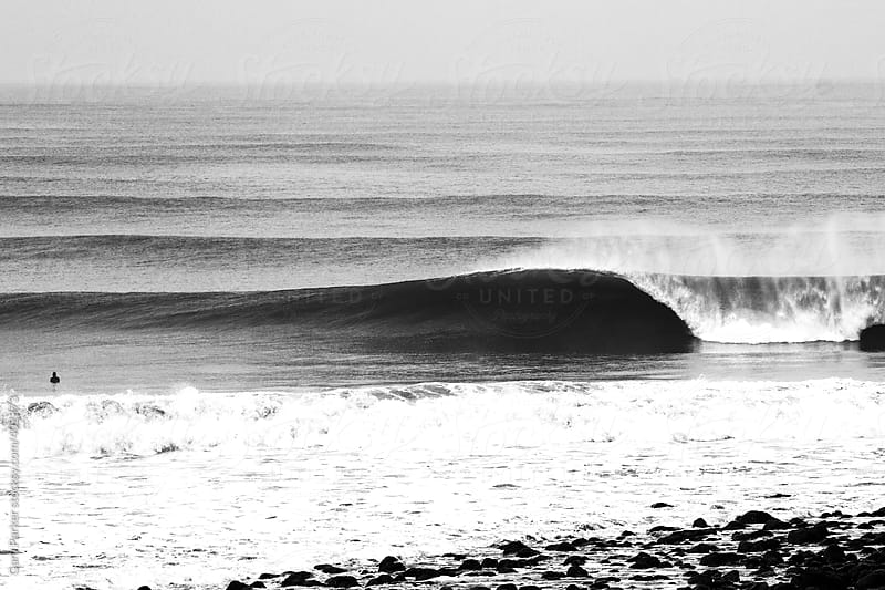 Black and white photo of a perfect wave and surfer by Gary Parker for Stocksy United