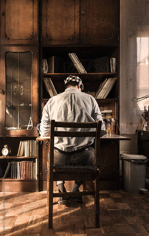 Look from behind on stylish oldfashioned male siting and working in old rustic studio. by Audrey Shtecinjo for Stocksy United