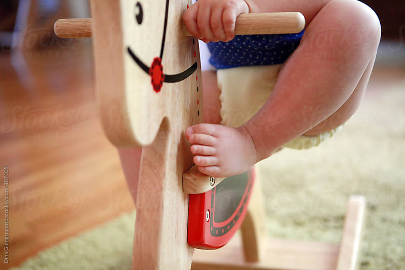 Lower torso of toddler sitting on rocking horse  by Dina Giangregorio for Stocksy United