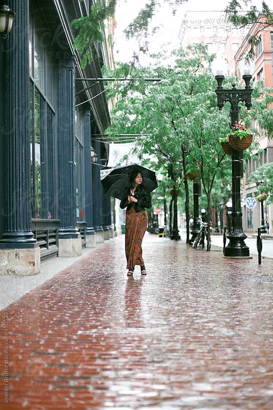 Woman in formal dress standing on cobblestone sidewalk in rain.  by Jennifer Brister for Stocksy United