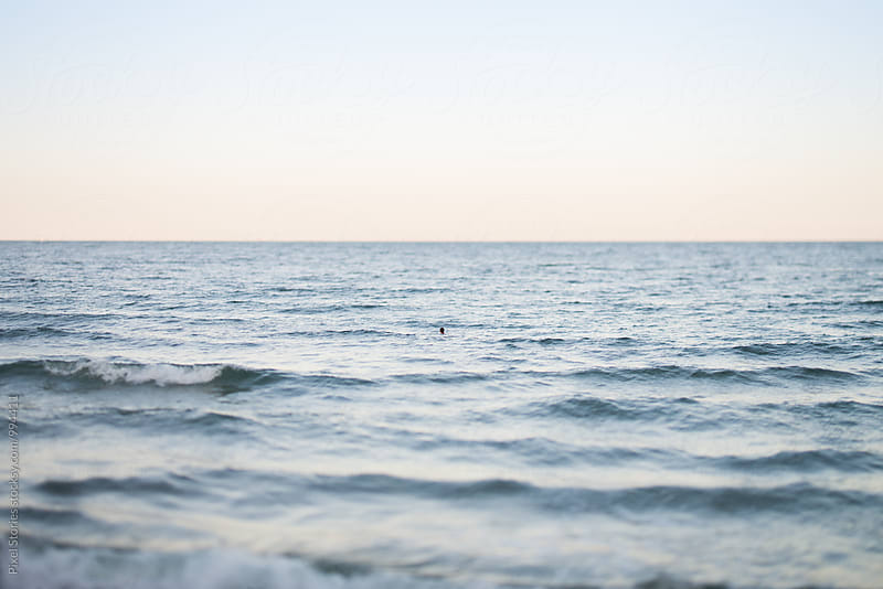 Unrecognizable person swimming in the sea by Pixel Stories for Stocksy United