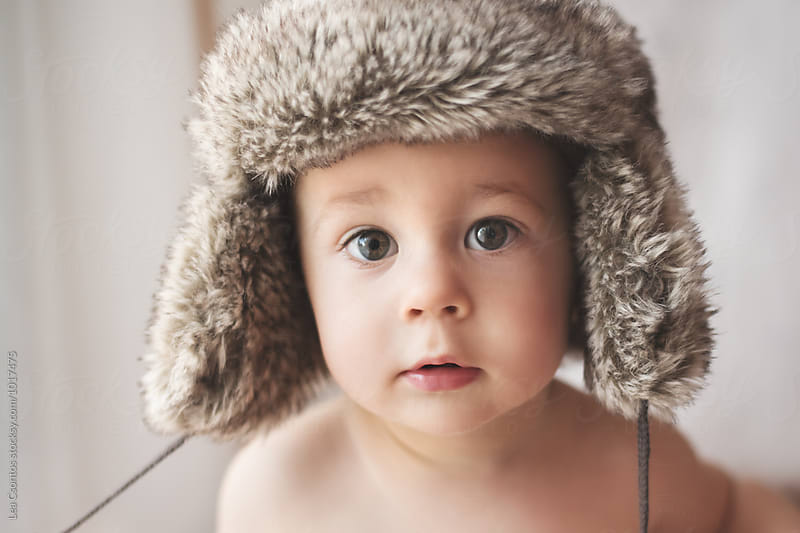 Portrait of a cute young boy wearing a furry winter hat by Lea Csontos for Stocksy United