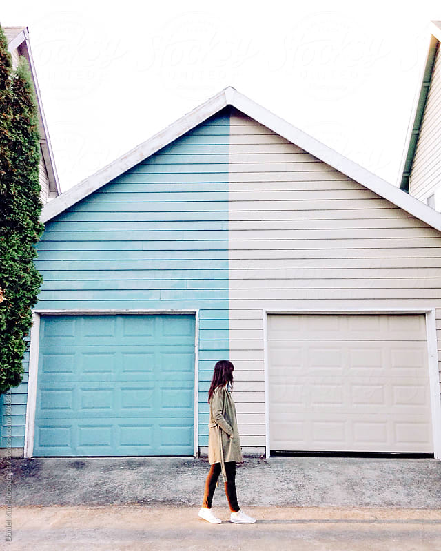 Woman walking in front of garages by Daniel Kim Photography for Stocksy United