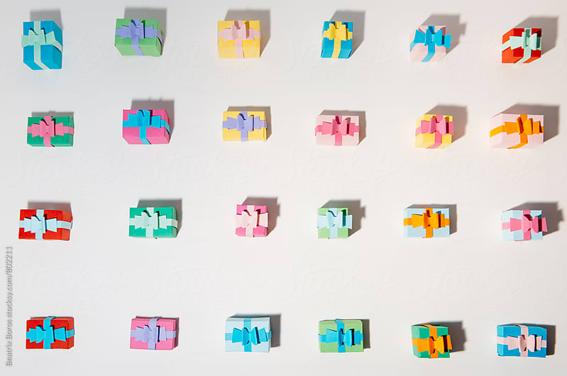 Small gift boxes in arranged order on white background by Beatrix Boros for Stocksy United