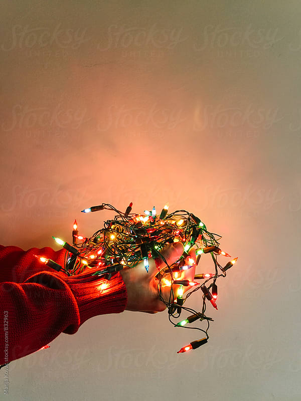 Male hands holding a christmas lights - vertical  by Marija Kovac for Stocksy United