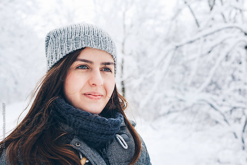 Portrait of happy woman wearing knit hat in snowy field by Borislav Zhuykov for Stocksy United