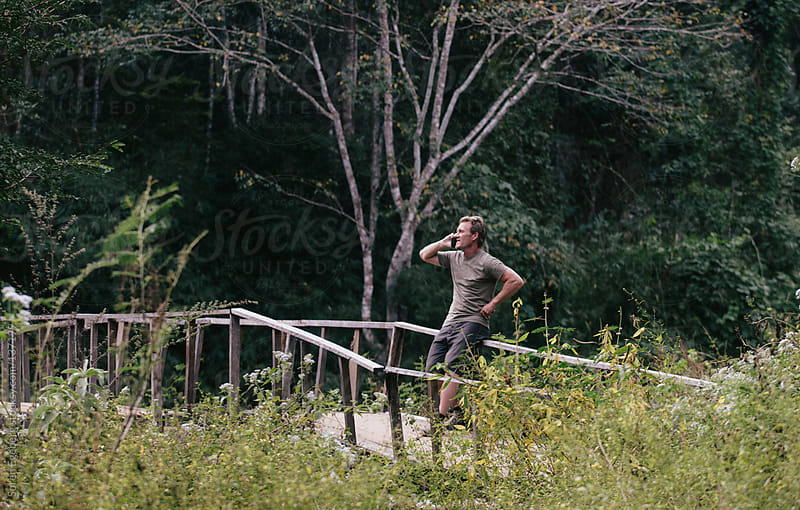 Man sitting on a fence in the forest talking on mobile phone. by Soren Egeberg for Stocksy United