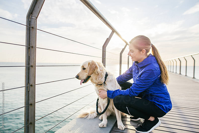 Portrait of a runner woman with her dog on a bridge.  by BONNINSTUDIO for Stocksy United