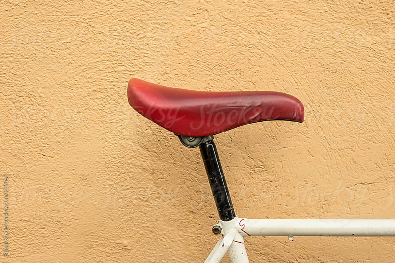 Closeup of a white vintage bicycle with red saddle by Bisual Studio for Stocksy United