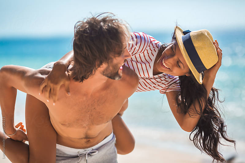 Couple Having Fun on the Beach by Lumina for Stocksy United