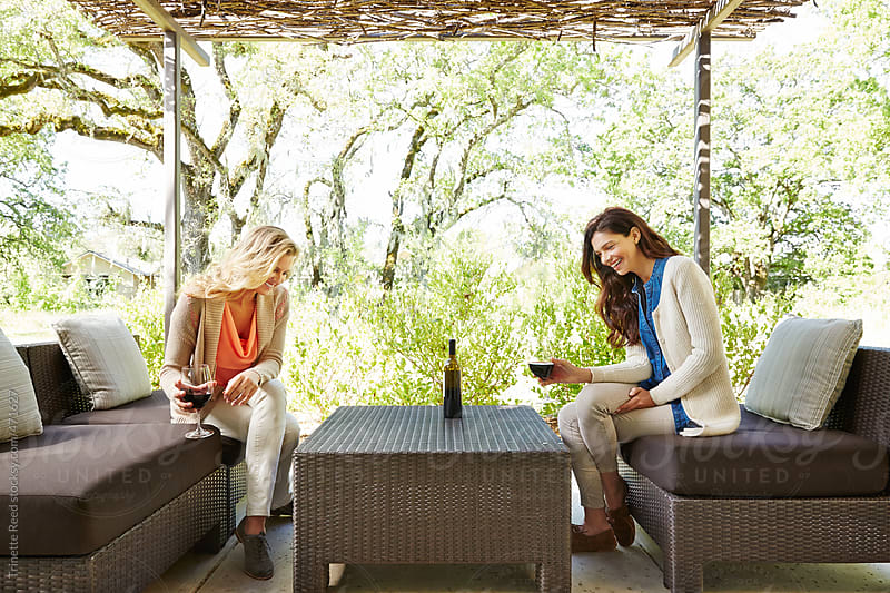 Girlfriends relaxing on outdoor porch with wine.  by Trinette Reed for Stocksy United