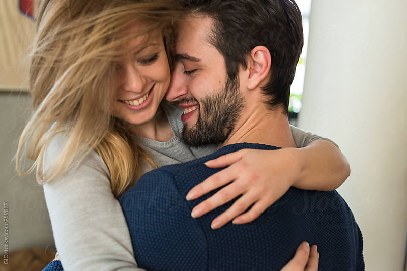 Happy young couple hugging at home by GIC for Stocksy United