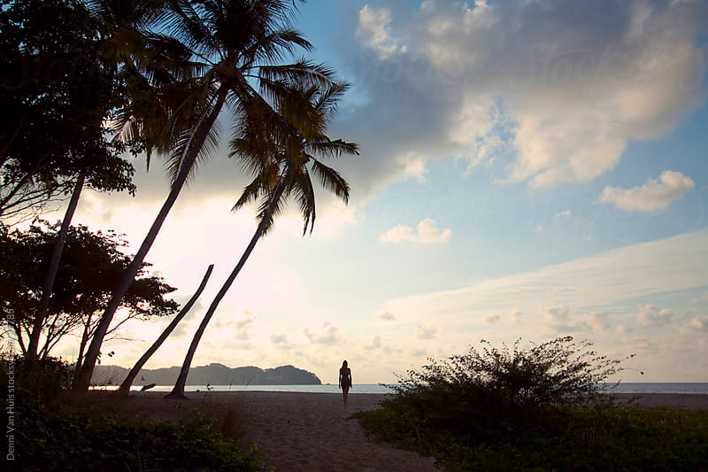 Young woman walks on a tropical beach while the sun sets by Denni Van Huis for Stocksy United
