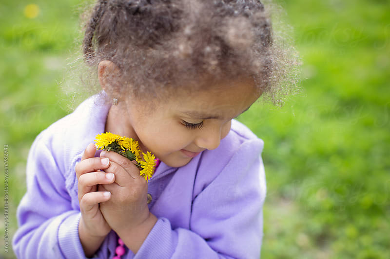 Portrait of a lovely young girl in a lavender coat lovingly holding a bundle of yellow dandelion flowers by anya brewley schultheiss for Stocksy United