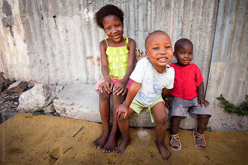Three Cute African kids sitting outside their home by Micky Wiswedel for Stocksy United