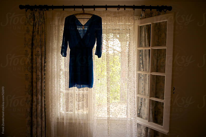 Dress hanging in front of a window by Freek Zonderland for Stocksy United