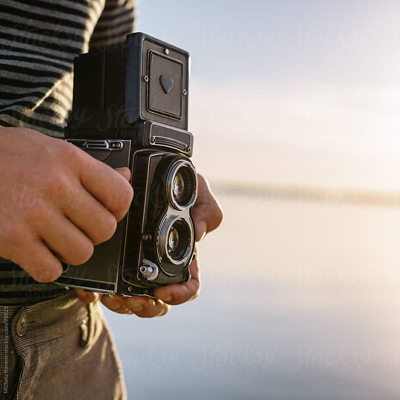 Man holding an old camera by michela ravasio for Stocksy United