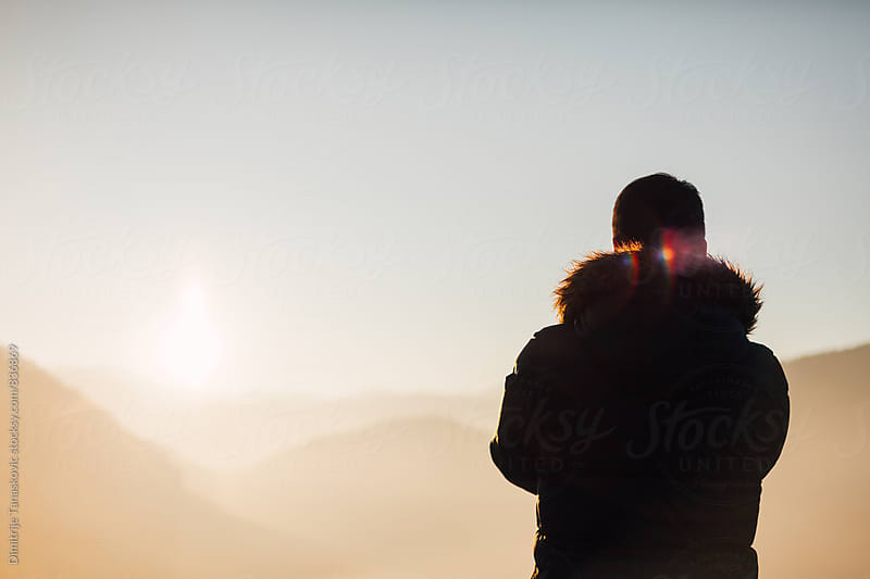 Man enjoying the view of the sunset above the mountains by Dimitrije Tanaskovic for Stocksy United