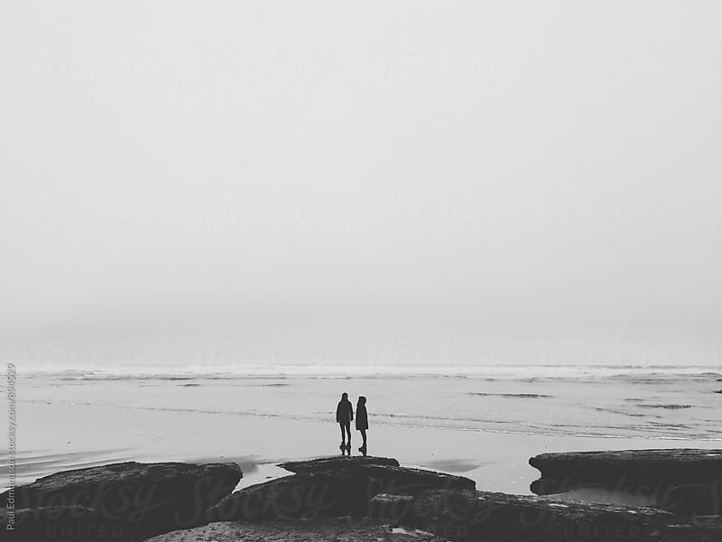 Mother and daughter standing on overcast beach, ocean in distance by Paul Edmondson for Stocksy United