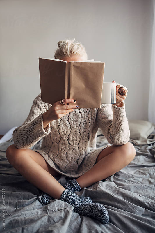 Woman Reading a Book and Having Coffee in Bed by Lumina for Stocksy United
