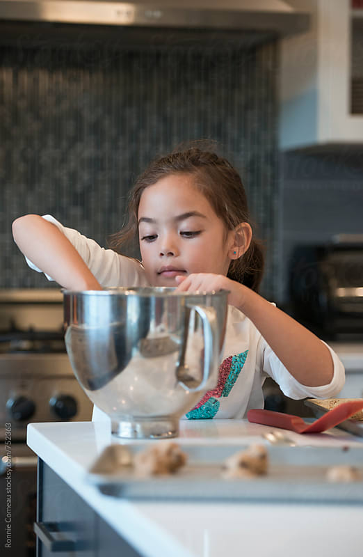 Little Girl Making Cookies by Ronnie Comeau for Stocksy United