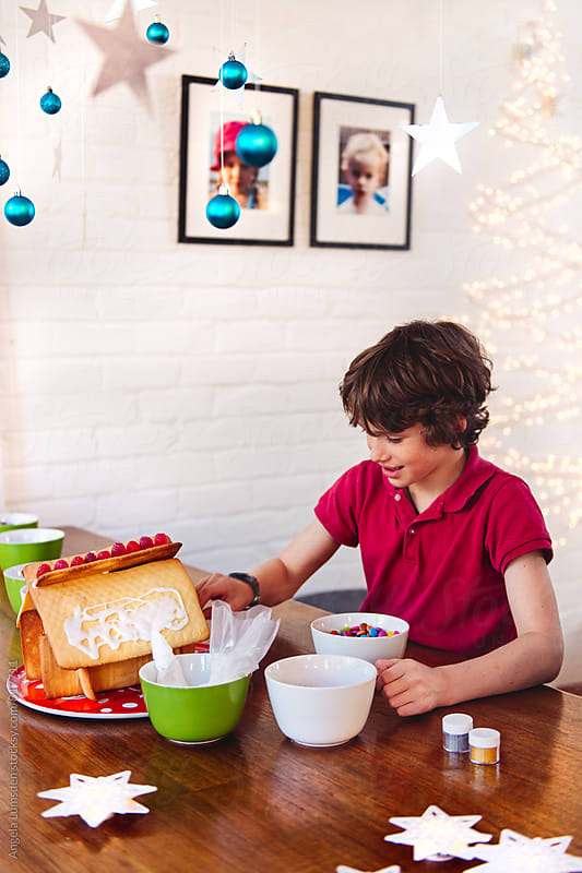 Decorating a home made ginger bread house by Angela Lumsden for Stocksy United