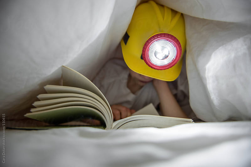 Boy wearing headlamp reads a book under the covers of his bed by Cara Dolan for Stocksy United